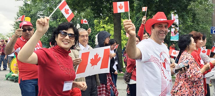 ISSofBC volunteers wave flags on Canada Day