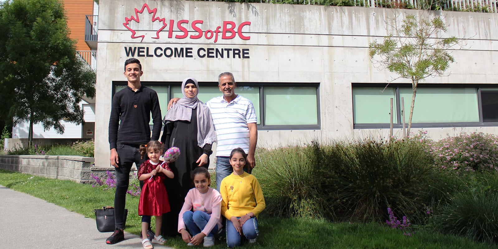 Refugee Family pose outside of ISSofBC Welcome Centre